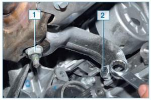 Накидным ключом или головкой «на 16» отворачиваем на несколько витков резьбы гайку 1 крепления кронштейна к коллектору и болт 2 крепления кронштейна к блоку цилиндров