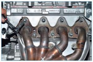 Высокой головкой «на 10» отворачиваем девять гаек крепления выпускного коллектора к шпилькам головки блока цилиндров