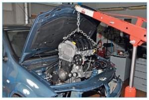 С помощью подъемного устройства поднимаем и вынимаем двигатель из моторного отсека.