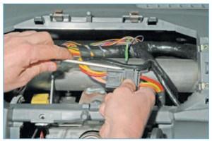 Поддев шлицевой отверткой фиксатор колодки жгута проводов, сдвигаем фиксатор