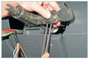 Установив ключ зажигания в положение между метками «А» и «М» (нанесенными на торце выключателя), пинцетом утапливаем два фиксатора выключателя…