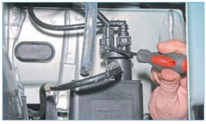 Отверткой отжимаем фиксатор колодки жгута проводов системы управления двигателем (для наглядности передний бампер снят)