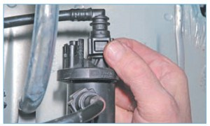 Сжав фиксаторы наконечника трубки, соединяющей электромагнитный клапан продувки адсорбера с впускным трубопроводом