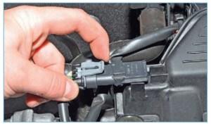 …отжав фиксатор колодки жгута проводов системы управления двигателем