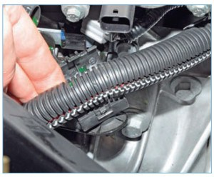 Расстегиваем пластмассовый держатель крепления жгута проводов системы управления двигателем…