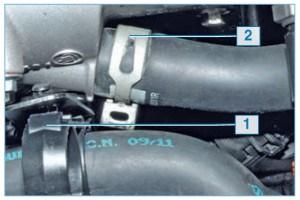 Преодолев сопротивление фиксаторов, вынимаем держатель 1 шлангов системы охлаждения из отверстий кронштейна. Сжав концы хомута 2, сдвигаем хомут по шлангу и снимаем шланг отопителя с патрубка корпуса термостата.