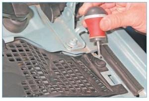 Поддеваем отверткой штифт пистона крепления левой накладки…