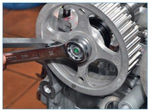 Опираясь на спицу шкива лезвием отвертки, стержнем отвертки надавливаем на ключ и поворачиваем его против часовой стрелки