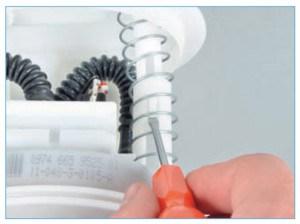 Отверткой отжимаем фиксатор крышки топливного модуля