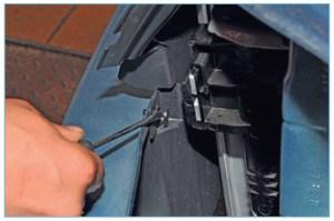 Отверткой сдвигаем фиксатор левого верхнего пистона крепления дефлектора радиатора к верхней поперечине радиатора