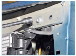 Головкой «на 10» отворачиваем болт крепления левого кронштейна верхнего крепления радиатора