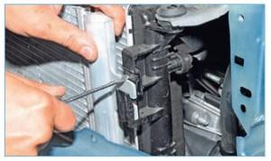 …отверткой поджимаем фиксатор верхнего кронштейна конденсатора и нижнего (на фото не виден).