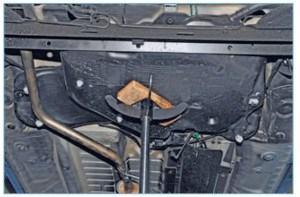 Устанавливаем регулируемый упор под топливный бак, подложив деревянный брусок чтобы не повредить бак