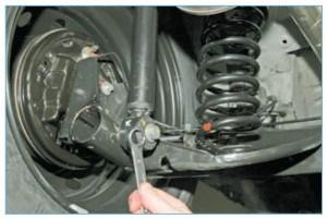 Снизу автомобиля накидным ключом или головкой «на 18» отворачиваем болт нижнего крепления амортизатора к рычагу балки…