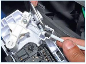 С помощью отвертки отжимаем фиксатор и выводим оболочку тяги привода заслонок распределения потоков воздуха из держателя