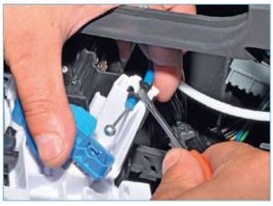 С помощью отвертки выводим оболочку тяги привода заслонки регулятора температуры воздуха из держателя