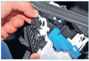 Выводим оболочку тяги привода заслонки рециркуляции воздуха из держателя