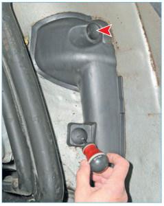 Шлицевой отверткой отворачиваем два пистона крепления защитного кожуха жгута проводов датчика