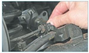 Выводим резиновую муфту жгута проводов датчика из держателя на рычаге задней подвески
