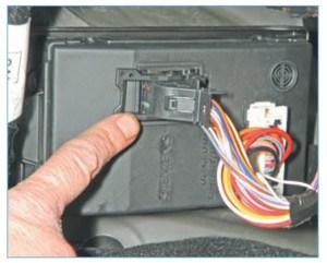…и поворачивая скобу фиксатора, отсоединяем колодку жгута проводов от блока