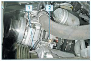 Отсоединяем наконечник провода 1 от вывода электромагнитной муфты компрессора и головкой «на 10» отворачиваем болт 2 крепления кронштейна шланга высокого давления