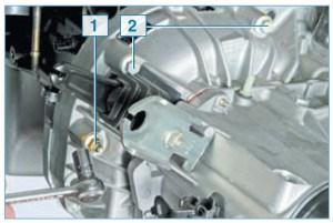 Головкой «на 13» отворачиваем гайку 1 и два болта 2 крепления коробки передач к блоку цилиндров (для наглядности показано на снятом силовом агрегате)