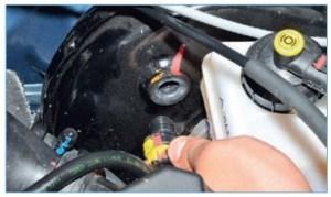 Преодолев сопротивление фиксаторов, вынимаем обратный клапан из уплотнительной втулки корпуса вакуумного усилителя тормозов