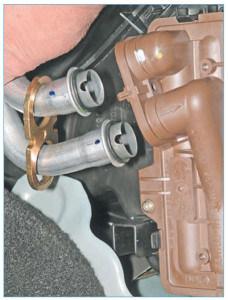 Вынимаем трубки из отверстий бачка радиатора отопителя