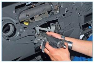 Перемещая верхнюю часть рулевой колонки так, чтобы она не зацепилась за элементы панели приборов и поперечной балки, вынимаем колонку через отверстие в панели приборов