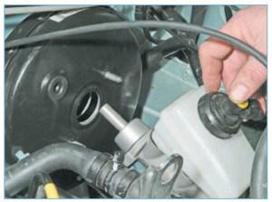 Осторожно изгибая тормозные трубки, снимаем со шпилек вакуумного усилителя главный тормозной цилиндр (в сборе с бачком) и отводим в сторону