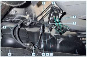 Расположение регулятора давления в гидроприводе тормозных механизмов задних колес: 1 – балка задней подвески; 2 – шланги тормозных механизмов задних колес; 3 – трубки тормозных механизмов задних колес; 4 – регулятор давления; 5 – трубки подвода тормозной жидкости к регулятору давления; 6 – скоба регулятора; 7 – регулировочная гайка шпильки регулятора; 8 – нажимной рычаг; 9 – регулировочная втулка тяги; 10 – тяга