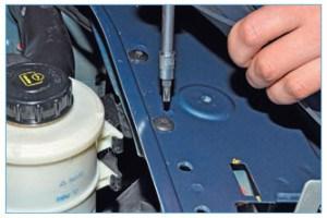 Отогнув верхнюю правую часть переднего бампера, тем же инструментом отворачиваем два винта крепления кронштейна бачка гидроусилителя рулевого управления