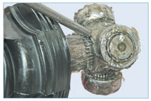 Нанося удары по торцу трехшиповика через выколотку из мягкого металла, сбиваем трехшиповик с вала