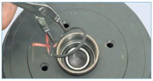 С наружной стороны барабана специальными щипцами для снятия стопорных колец снимаем стопорное кольцо подшипника