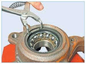 Щипцами для снятия стопорных колец вынимаем стопорное кольцо подшипника из канавки поворотного кулака