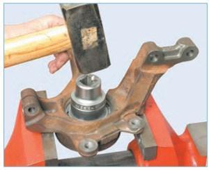 Нанося удары по торцу наружного кольца подшипника через оправку или головку подходящего размера, выпрессовываем подшипник из кулака