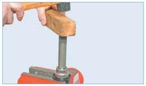 Нанося удары молотком через деревянный брусок в торец вала…