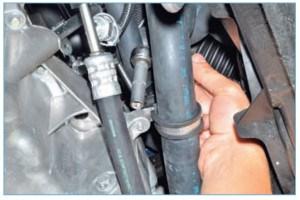 …головкой «на 10» отворачиваем болт крепления держателя отводящего шланга радиатора к поддону картера