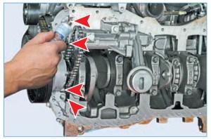 …в четырех местах передней крышки блока цилиндров (для наглядности показано на демонтированном двигателе)