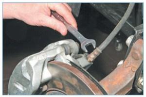 Ключом «на 14» выворачиваем нижний наконечник шланга из отверстия корпуса цилиндра тормозного механизма переднего колеса…