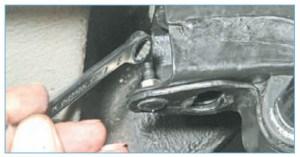 Накидным ключом «на 10» отворачиваем гайку крепления скобы подушки к подрамнику