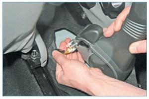 Приподняв рычаг стояночного тормоза, отсоединяем колодку проводов от выключателя сигнализатора стояночного тормоза