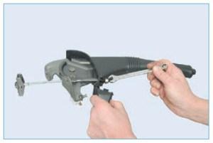 Отведя заглушку облицовки рычага, ключом «на 10» полностью отворачиваем регулировочную гайку на резьбовом наконечнике переднего троса