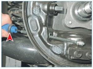 …выводим наконечник из отверстия в щите тормозного механизма…