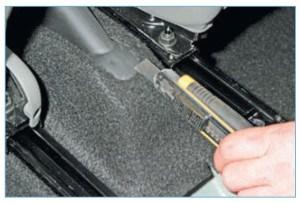 Ножом аккуратно разрезаем ковровое покрытие пола за рычагом стояночного тормоза
