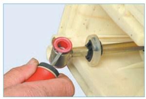 Отверткой поддеваем втулки (для наглядности показано на снятом механизме управления коробкой передач)…