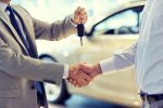Менеджер автосалона передает клиенту ключи от нового автомобиля
