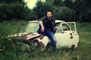 Мужчина на фоне ржавой машины